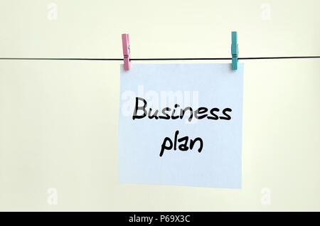 Business plan. Note is written on a white sticker that hangs with a clothespin on a rope on a background of beige wall . - Stock Photo