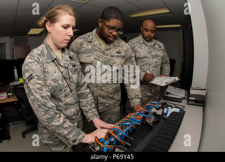 U.S. Air Force Staff Sgt. Tajwalid, quality assurance officer for the 363rd Intelligence, Surveillance and Reconnaissance Wing, evaluates Airmen 1st Class Jenny and William, cyber systems operators assigned to the 363rd Intelligence Support Squadron, as they perform tasks for cloning hard drives at Langley Air Force Base, Va., May 24, 2016. Cyber system operators must quickly respond to service outages and interruptions to network operations. (U.S. Air Force photo by Airman 1st Class Derek Seifert) - Stock Photo