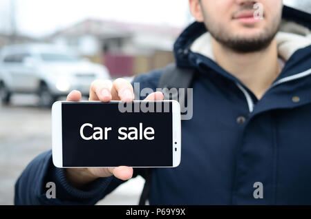 A young guy shows an inscription on the smartphone's display on the background of a car and a big house in winter. Car sale  . - Stock Photo