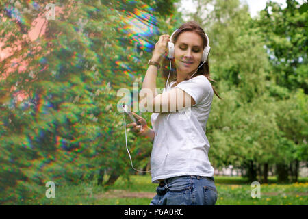 Young pregnant girl listens to music on headphones in a city park. She is holding a cell phone in her T-shirt and jeans. Online radio. Blur effect - Stock Photo