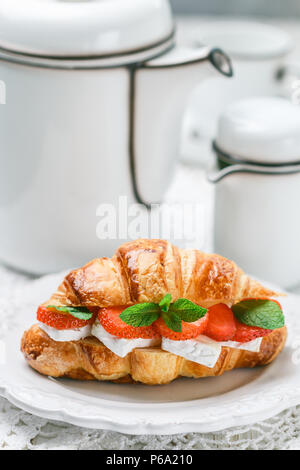 Croissant with strawberries, brie cheese or Camambert and mint. Delicious gourmet Breakfast. Selective focus - Stock Photo