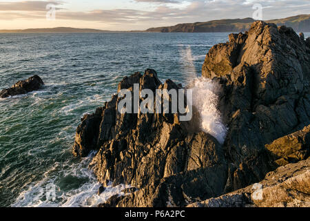 This is a view of a wave crashing onto rocks on the ocean edge.  It was taken in Donegal Ireland at sunset - Stock Photo