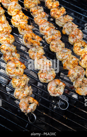 Shrimp skewered and cooking on a outdoor charcoal barbecue in southern California USA - Stock Photo
