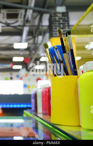 Art paint brushes in cup are located in the children's entertainment hall . - Stock Photo