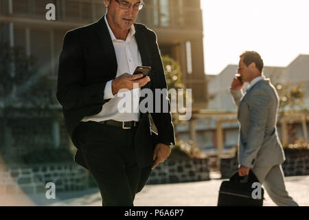 Businessman looking at his mobile phone while walking on street to office. Busy office going people carrying office bag and using mobile phone. - Stock Photo
