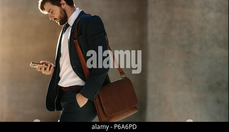 Businessman looking at his mobile phone while walking on street to office. Busy office going man commuting to office carrying his office bag and using - Stock Photo