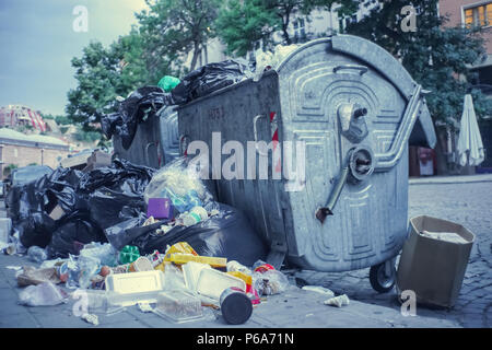 Garbage container overflowing in a city street - Stock Photo