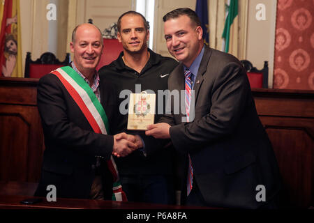 """Dr. Luigi Salvatore Bonelli, the mayor of Nicosia, Italy, hands off an award to Navy Lt. Arthur Briggs, the chaplain of Special Purpose Marine Air-Ground Task Force Crisis Response-Africa, and 1st Lt. Eric Abrams, the public affairs officer for SPMAGTF-CR-AF, in the Plazzo de Centro during a community project in Nicosia, Italy, May 25, 2016.  Students from Instituto di Istruzione Superiore """"Alessandro Volta"""" were able to practice their English and share their culture while leading Marines and sailors on a tour around Nicosia. (U.S. Marine Corps photo by Cpl. Alexander Mitchell/released) - Stock Photo"""