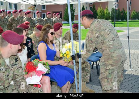 Wife of incoming commander Capt. Tyler Martin, receives a bouquet of yellow roses from a paratrooper during the change of responsibility ceremony for Company B, 2nd Battalion, 503rd Infantry Regiment, 173rd Airborne Brigade, May 26, 2016 at Caserma Del Din in Vicenza, Italy. The 173rd Airborne Brigade based in Vicenza, Italy, is the Army Contingency Response Force in Europe, and is capable of projecting forces to conduct the full of range of military operations across the United State European, Central and Africa Commands areas of responsibility.(U.S. Army photo by Visual Information Specialis - Stock Photo