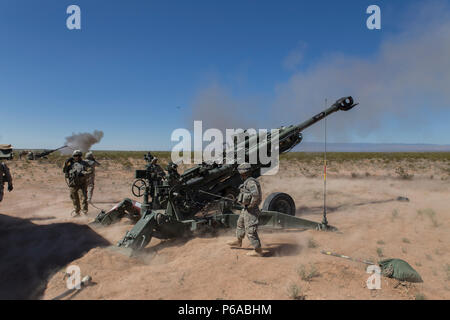 Soldiers assigned to 2nd Battalion, 3rd Field Artillery Regiment, 1st Brigade Combat Team, 1st Armored Division, fire a M777 Howitzer during Hustler Trough III May 23 at the Orogrande Range Complex, N.M. - Stock Photo