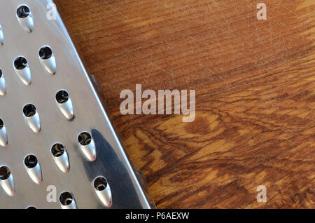 The chrome grater lies on the cutting board with a lot of scars from the ax and knife. Background image for cooking recipes . - Stock Photo