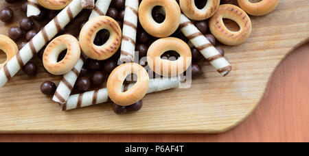 Crispy tubules, chocolate melting balls and bagels lie on a wooden surface. Mix of various sweets . - Stock Photo