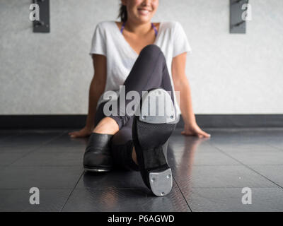 Smiling teenage tap dancer sitting cross legged in dance class relaxing - Stock Photo
