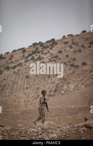 A soldier from the Nineveh Plain Protection Unit patrols the mountainside during a react to contact training exercise at their training facility in the Nineveh Province, May 18, 2016.  The NPPU are a small group of fighters who came together to protect their people in the fight against the Islamic State of Iraq and the Levant.  Training focused on the Combined Joint Task Force – Operation Inherent Resolve overall mission to build partner capacity and increase the military capacity of local forces fighting ISIL.  (U.S. Army photo by Staff Sgt. Sergio Rangel/RELEASED) - Stock Photo