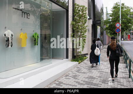 Pedestrians walk past an Issey Miyake store in Aoyama which has a minimalist T-shirt window display. - Stock Photo