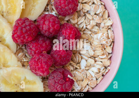 Close up of oatmeal in a beautiful pink bowl with fresh sweet rasberry and banana slices on turquoise background. - Stock Photo