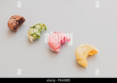 delicious colorful bitten macaroons with cracks and cream on trendy pastel gray paper. eating tasty pink, yellow, green and brown macarons. space for  - Stock Photo
