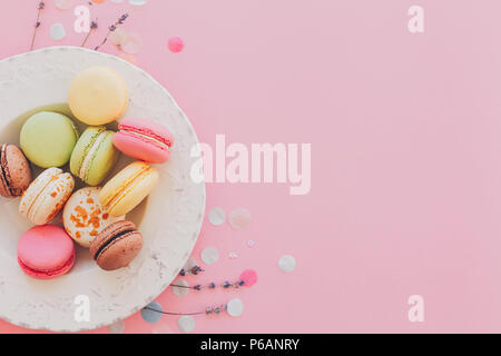 delicious colorful macaroons in vintage white plate on trendy pastel pink paper, stylish flat lay. tasty pink, yellow, green and brown macarons with l - Stock Photo