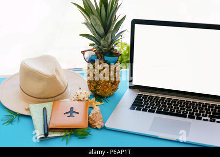 planning summer vacation concept. laptop with empty screen, pineapple in sunglasses,  passport, map, hat,  on blue trendy paper with shells. space for - Stock Photo
