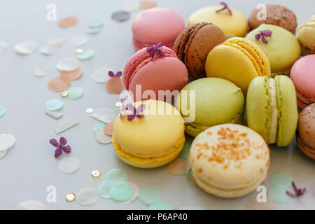 colorful macarons on trendy pastel gray paper with lilac flowers and confetti. tasty pink, yellow, green and brown macaroons. candy bar for party. foo - Stock Photo