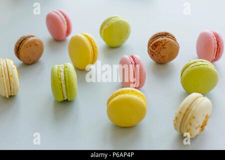 colorful macarons on trendy pastel gray paper. tasty pink, yellow, green and brown macaroons. candy bar for party. instagram food photography. yummy b - Stock Photo