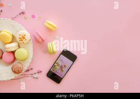 instagram food photography of tasty colorful macarons in plate and phone on trendy pastel pink paper flat lay. space for text. modern photo workshop.  - Stock Photo