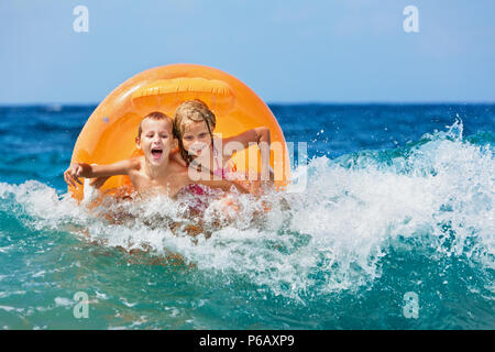 Happy kids have fun in sea surf on beach. Joyful couple of children on inflatable ring ride on wave. Travel lifestyle, swimming activities on holidays - Stock Photo