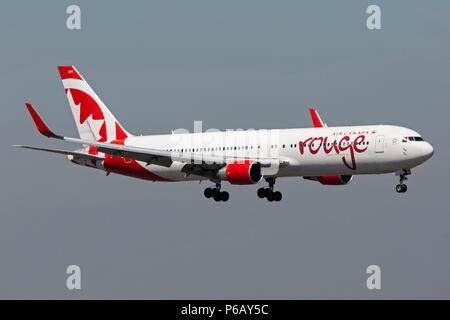 An Air Canada Rouge Boeing 767 prepares to land at Manchester Airport in England. - Stock Photo