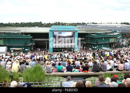View from the summit of Henman Hill ( Murray Mount ) over Wimbledon Lawn Tennis Club. Supporters concentrating on the big screen. Great atmosphere. - Stock Photo
