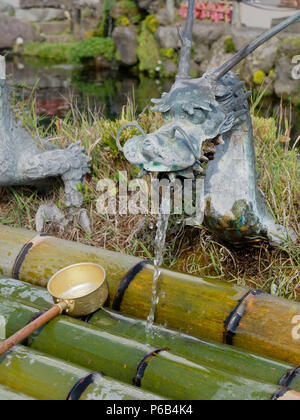 YAMANASHI, JAPAN - SEPTEMBER 26, 2017 : Spring water from dragon ornament tap of Waku pond is one of the main tourist attraction in Oshino Hakkai or springs of Mount Fuji, Oshino village - Stock Photo