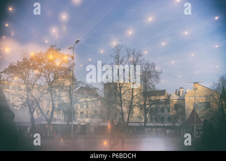 Mysterious reflection of the square with the yellow lights of the city of Riga in the window glass in the afternoon late autumn - Stock Photo