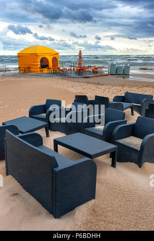 Wicker black tables and armchairs with a yellow summer cafe tent in a storm on the sandy beach of the Baltic Sea in summer - Stock Photo