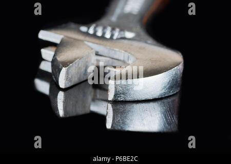 adjustable wrench closeup on black background maintenance - Stock Photo