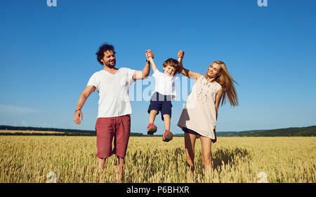 Happy family having fun playing in the field . - Stock Photo