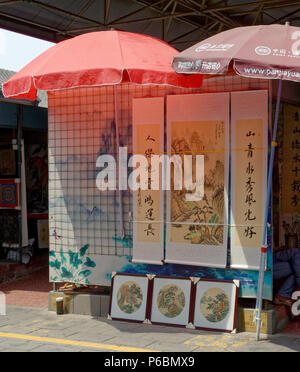 Traditional Chinese art on sale at the very busy Panjiayuan Antique Market in Beijing, China - Stock Photo