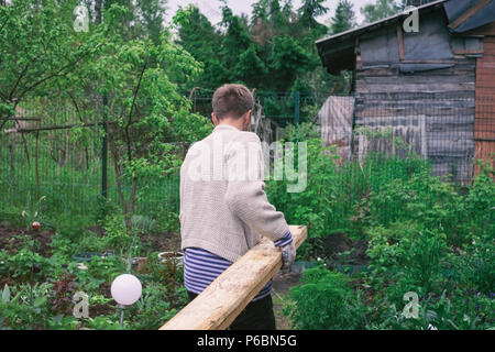 Man carry timber for new house. Back view - Stock Photo