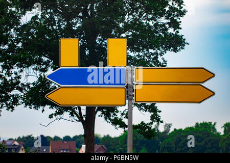 Blank directional road signs against park.  metal arrows on the signpost. - Stock Photo