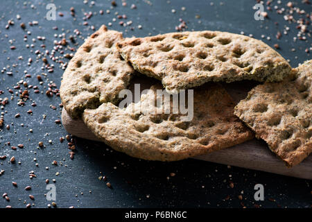 closeup of a kale flatbread, broken in some pieces, on a chopping board, placed on a dark green rustic wooden table - Stock Photo
