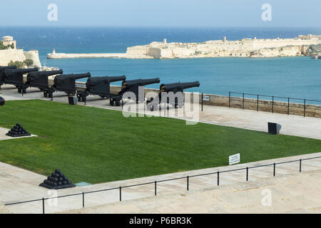 View over artillery guns of the Saluting Battery artillery battery which fire the 4pm time signal gun every day over the Grand harbour, in Valletta, Malta. (91) - Stock Photo