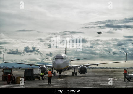 The air traffic controller takes care of landing an airplane at the airport, while another is flying in the sky - Stock Photo