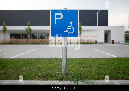 Disabled traffic sign at an empty car park represent handicap parking space without car or people - Stock Photo