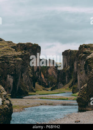 fjadrargljufur canyon in iceland with blue water and cloudy sky. really beautiful canyon vertically - Stock Photo