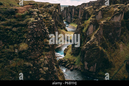 fjadrargljufur canyon in iceland with blue water and cloudy sky. really beautiful canyon no people - Stock Photo