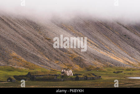 old viking village in iceland with foggy hill. old wooden buildings covered grass - Stock Photo
