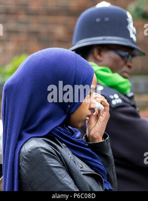 The first anniversary of the 24-storey Grenfell Tower block of public housing flats fire which claimed 72 lives. Young female wipes tears away during the public memorial service, South Kensington, London, UK, 14th June 2018. - Stock Photo