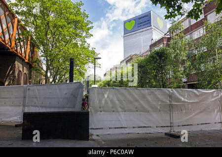 The first anniversary of the 24-storey Grenfell Tower block of public housing flats fire which claimed 72 lives. The burnt out shell has now been covered in a white tarpaulin with the message 'Grenfell Forever in Our Hearts' South Kensington, London, UK, 14th June 2018. - Stock Photo