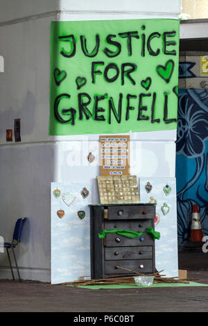 The first anniversary of the 24-storey Grenfell Tower block of public housing flats fire which claimed 72 lives. Justice for Grenfell sign near a makeshift memorial under the Westway flyover.  South Kensington, London, UK, 14th June 2018. - Stock Photo