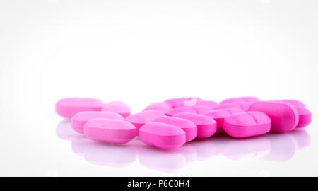 Pile of pink tablets pill isolated on white background. Norfloxacin 400 mg for treatment cystitis. Antibiotics drug resistance. Pink pills symbol of r - Stock Photo