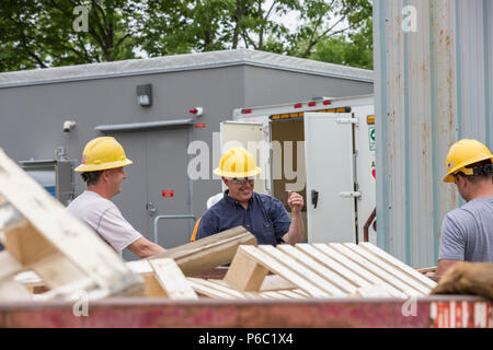 Engineers putting pallets into a dumpster - Stock Photo