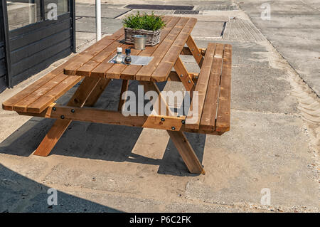 wooden bench on a concrete floor near the beach - Stock Photo